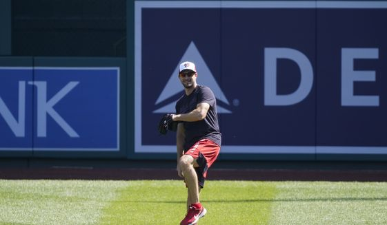 Washington Nationals starting pitcher Max Scherzer throws during a baseball workout at Nationals Park, Monday, April 5, 2021, in Washington. The Nationals are scheduled to play the Braves on Tuesday. (AP Photo/Alex Brandon)