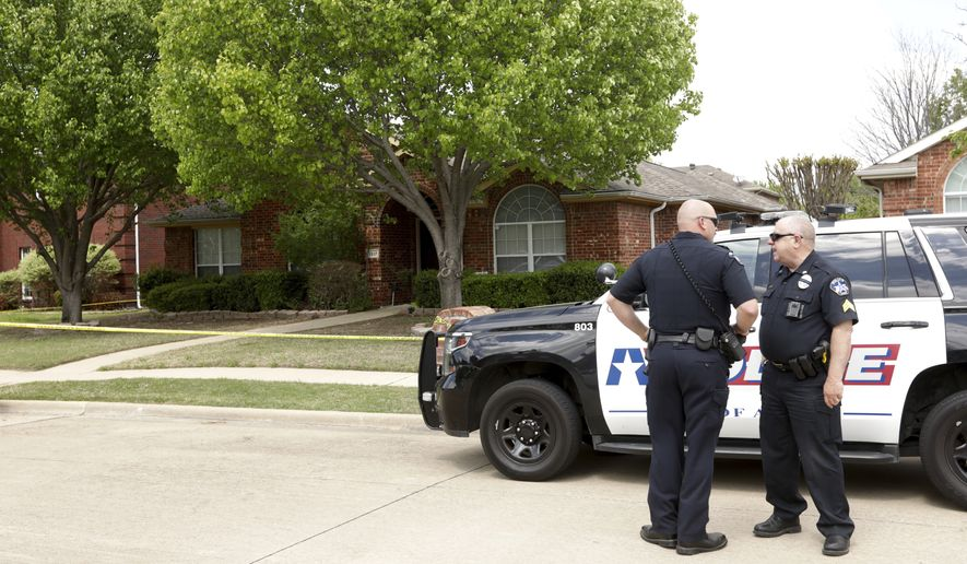 Police stand at the scene on Pine Bluff, Monday, April 5, 2021, in Allen, Texas, where six people were found fatally shot in the suburban Dallas home after police said two brothers made a plan to kill four family members and themselves. (Jason Janik/The Dallas Morning News via AP)