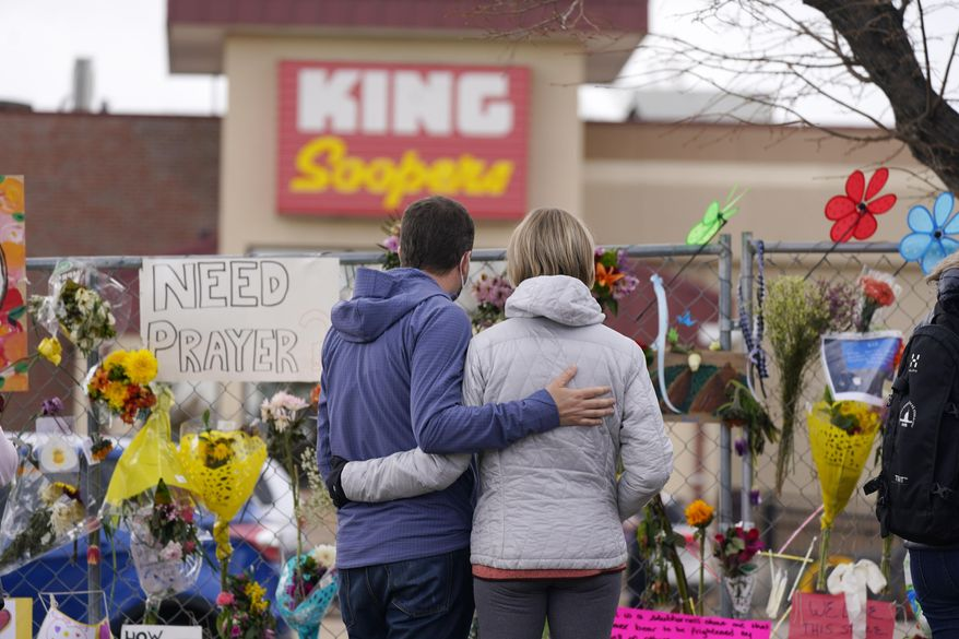 Mourners walk the temporary fence line outside the parking lot of a King Soopers grocery store, the site of a mass shooting in which 10 people died, Friday, March 26, 2021, in Boulder, Colo. (AP Photo/David Zalubowski)