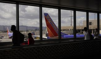 Passengers walk past a Southwest Airlines plane at Sky Harbor International Airport in Phoenix, Friday, March 26, 2021. (AP Photo/Sue Ogrocki)