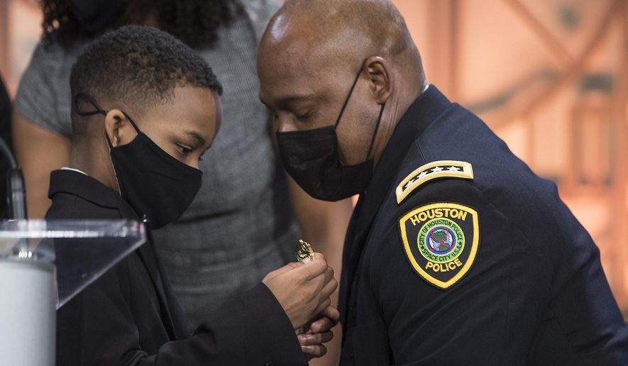 Houston Police Chief Wyatt Finner, left, pins the chief's badge on the uniform of his dad, new Houston Police Chief Troy Finner, during a ceremony at City Hall Monday, April 5, 2021, in Houston. Finner is a 54-year-old veteran who hails from Fifth Ward and attended Madison High School in Houston. He formally takes the reins of the police department, the same day that outgoing Chief Art Acevedo is sworn in as chief in Miami. (Brett Coomer/Houston Chronicle via AP)