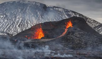 The Lava flows from an eruption of a volcano on the Reykjanes Peninsula in southwestern Iceland on Wednesday, March 31, 2021. Iceland's latest volcano eruption is still attracting crowds of people hoping to get close to the gentle lava flows. (AP Photo/Marco Di Marco)