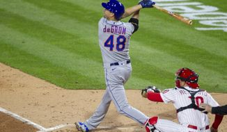 New York Mets Jacob deGrom (48) follows through on an RBI single during the fourth inning of a baseball game against the Philadelphia Phillies, Monday, April 5, 2021, in Philadelphia. (AP Photo/Laurence Kesterson)