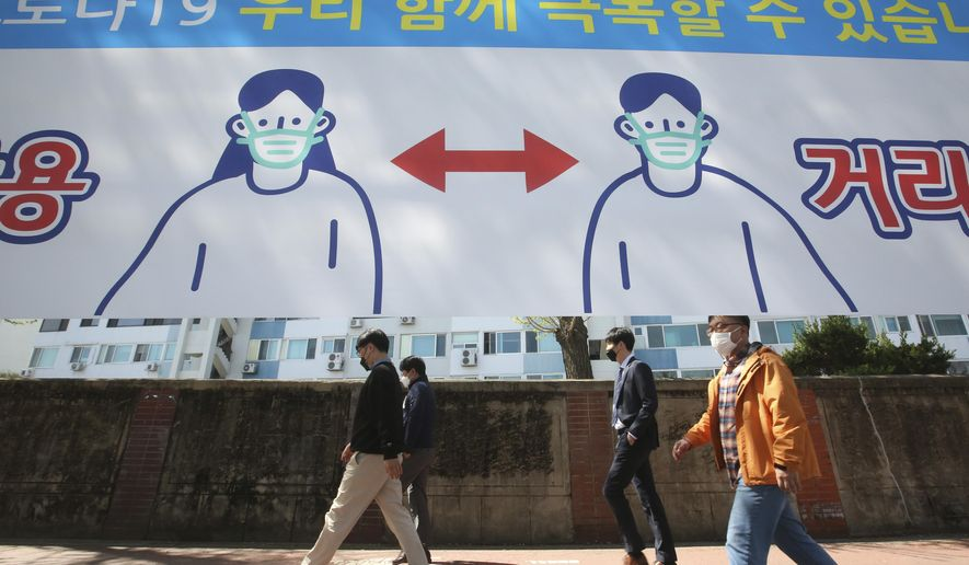 """People wearing face masks pass by a banner displaying precautions against the coronavirus on a street in Seoul, South Korea, Monday, April 5, 2021. The banner reads """" We can overcome Corona 19."""" (AP Photo/Ahn Young-joon)"""