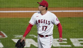 Los Angeles Angels starting pitcher Shohei Ohtani walks off the field during the fifth inning of the team's baseball game against the Chicago White Sox on Sunday, April 4, 2021, in Anaheim, Calif. Ohtani and White Sox's Jose Abreu collided at the plate while Ohtani was covering after a passed ball. Abreu and Adam Eaton both scored. Ohtani left the game. (AP Photo/Ashley Landis)