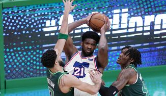 Philadelphia 76ers center Joel Embiid, center, looks to pass while pressured by Boston Celtics forward Jayson Tatum, left, and center Robert Williams III, right, during the first half of an NBA basketball game, Tuesday, April 6, 2021, in Boston. (AP Photo/Charles Krupa)