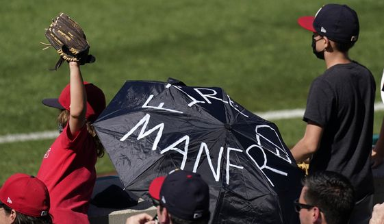 A fan unfurls an umbrella calling for the firing of Major League Baseball commissioner Rob Manfred as kids beg for a ball from players during the eighth inning of a baseball game Tuesday, April 6, 2021, in Anaheim, Calif. (AP Photo/Mark J. Terrill)