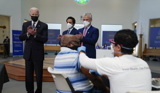 President Joe Biden applauds as a person receives a COVID-19 vaccination shot as he visits a vaccination site at Virginia Theological Seminary, Tuesday, April 6, 2021, in Alexandria, Va. (AP Photo/Evan Vucci)
