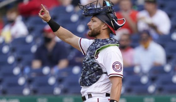 Washington Nationals catcher Jonathan Lucroy gestures in the seventh inning of an opening day baseball game against the Atlanta Braves at Nationals Park, Tuesday, April 6, 2021, in Washington. (AP Photo/Alex Brandon)