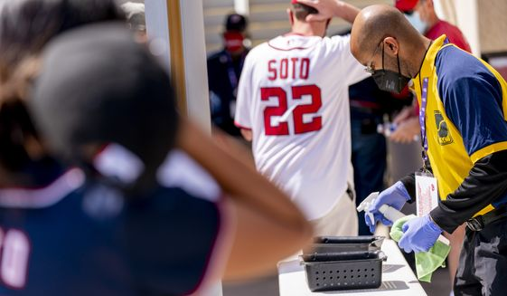 A worker sanitizes trays as fans go through security before the Washington Nationals play the Atlanta Braves in an opening day baseball game at Nationals Park, Tuesday, April 6, 2021, in Washington. (AP Photo/Andrew Harnik)