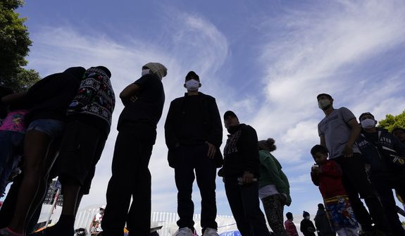 Migrants line up for a free meal at a makeshift camp of migrants at the border port of entry leading to the United States, Wednesday, March 17, 2021, in Tijuana, Mexico. The migrant camp shows how confusion has undercut the message from U.S. President Joe Biden that its not the time to come to the United States. Badly misinformed, some 1,500 migrants who set up tents across the border from San Diego harbor false hope that Biden will open entry briefly and without notice. (AP Photo/Gregory Bull) **FILE**