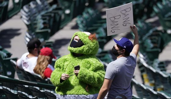 A fan wears an Oscar the Grouch costume as he taunts the Houston Astros prior to a baseball game against the Los Angeles Angels Tuesday, April 6, 2021, in Anaheim, Calif. (AP Photo/Mark J. Terrill)