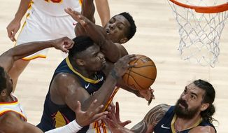 New Orleans Pelicans forward Zion Williamson (1) tries to get to the basket as Atlanta Hawks forward Onyeka Okongwu (17) defends in the first half of an NBA basketball game Tuesday, April 6, 2021, in Atlanta. (AP Photo/John Bazemore)
