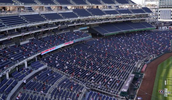 Fans sit socially distanced in the stands during an opening day baseball game between the Atlanta Braves and the Washington Nationals at Nationals Park, Tuesday, April 6, 2021, in Washington. (AP Photo/Alex Brandon)