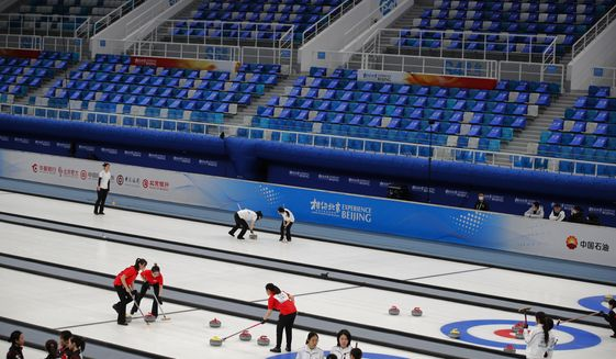 """Local teams compete in a curling competition during a test event for the 2022 Beijing Winter Olympics at the National Aquatic Center, also known as the """"Water Cube"""" in Beijing, Saturday, April 3, 2021. The organizers of the 2022 Beijing Winter Olympics has started 10 days of testing for several sport events in five different indoor venues from April 1-10, becoming the first city to hold both the Winter and Summer Olympics. (AP Photo/Andy Wong). **FILE**"""