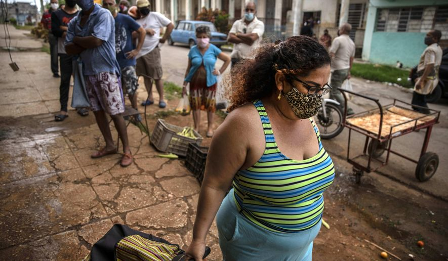 Yuliet Colon pulls her rolling grocery cart as she walks home after after a visit to the agro market in Havana, Cuba, Friday, April 2, 2021. Colon helps Cubans cope with shortages exacerbated by the new coronavirus pandemic with Facebook posts of culinary creations designed around what is actually available at the market. (AP Photo/Ramon Espinosa)