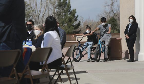 Two boys sit on their bikes as they watch Gov. Michelle Lujan Grisham prepare to sign a bill increasing school funding to communities with large tracts of federal land on Monday, April 5, 2021, in Santa Fe, New Mexico. At the event Lujan Grisham celebrated the reopening of in-person learning this week, including Albuquerque schools on Monday. They boys attend Santa Fe Public Schools, which resume Tuesday following the Easter break. (AP Photo/Cedar Attanasio)
