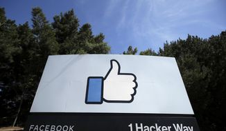 FILE - In this April 14, 2020, file photo, the thumbs up Like logo is shown on a sign at Facebook headquarters in Menlo Park, Calif. Facebook said Tuesday, April 6, 2021, it has removed hundreds of fake accounts linked to an Iranian exile group and a troll farm in Albania. (AP Photo/Jeff Chiu, File)
