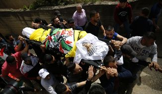 Palestinians carry the body of Osama Mansour during his funeral, in the village of Biddu near the West Bank city of Ramallah, Tuesday, April 6, 2021. Mansour was killed by Israel soldiers at a temporary vehicle checkpoint in the occupied West Bank near Jerusalem. The military said the soldiers thwarted an attempted car-ramming attack in the village of Bir Nabala. But the man's wife, who was in the car with him and was wounded by the gunfire, said the couple followed the soldiers' instructions and posed no threat. (AP Photo/Majdi Mohammed)