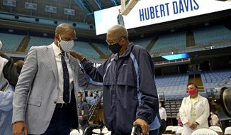 North Carolina head coach Hubert Davis, left, is congratulated by former North Carolina player Bill Chamberlain following a news conference at the University of North Carolina in Chapel Hill, N.C., Tuesday, April 6, 2021. Davis was named the Tar Heels' new NCAA men's basketball coach following the retirement of Roy Williams. (AP Photo/Gerry Broome)