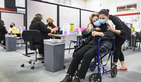 Manda Zand, right, hugs her grandmother Farang Ahmadkorour, 92, after she received her COVID-19 vaccine at the Seneca College mass vaccination site during the coronavirus pandemic in Toronto, Tuesday, April 6, 2021. (Nathan Denette/The Canadian Press via AP)