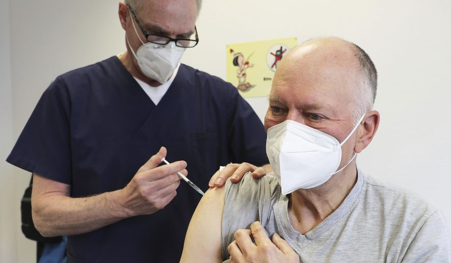 Manfred Haas, right, receives the AstraZeneca vaccine against the COVID-19 disease from his family doctor Oliver Funken in Rheinbach, Germany, Tuesday, April 6, 2021. In German federal state North Rhine-Westphalia, Corona vaccinations have started in GP surgeries. (Oliver Berg/dpa via AP)