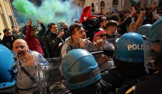 Demonstrators scuffle with Italian Policemen during a protest by Restaurant and shop owners outside the Lower Chamber in Rome, Tuesday, April 6, 2021. Demonstrators demanded to reopen their business and protested against restrictive measures of the Italian Government to cope with the surge of COVID-19 cases. (AP Photo/Andrew Medichini)