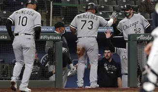 Chicago White Sox's Yermin Mercedes (73) and Yoan Moncada (10) are greeted at the dugout by pitching coach Ethan Katz (52) after they scored on a two-RBI single hit by Yasmani Grandal during the fifth inning of a baseball game against the Seattle Mariners, Monday, April 5, 2021, in Seattle. (AP Photo/Ted S. Warren)