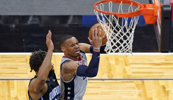 Washington Wizards guard Russell Westbrook, right, drives to the basket for a shot past Orlando Magic center Khem Birch during the first half of an NBA basketball game Wednesday, April 7, 2021, in Orlando, Fla. (AP Photo/John Raoux)