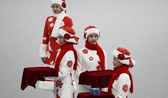 Chinese attendants dressed in winter costumes rehearse the award ceremony of the men's 500-meters race during a test event for the 2022 Beijing Winter Olympics at the National Speed Skating Oval in Beijing, Wednesday, April 7, 2021. The organizers of the 2022 Beijing Winter Olympics has started 10 days of testing for several sport events in five different indoor venues from April 1-10, becoming the first city to hold both the Winter and Summer Olympics. (AP Photo/Andy Wong)