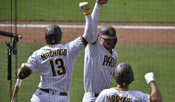 San Diego Padres' Wil Myers, back right, celebrates with Manny Machado after a solo home run during the eighth inning of the team's baseball game against the San Francisco Giants in San Diego, Wednesday, April 7, 2021. (AP Photo/Kelvin Kuo)