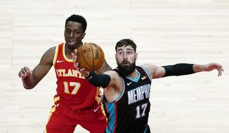 Memphis Grizzlies center Jonas Valanciunas (17) grabs a rebound in front of Atlanta Hawks forward Onyeka Okongwu (17) in the first half of an NBA basketball game Wednesday, April 7, 2021, in Atlanta. (AP Photo/John Bazemore)