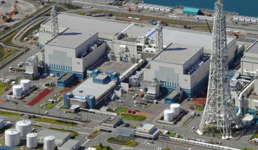FILE - This Sept. 30, 2017, aerial file photo shows the reactors of No. 6, right, and No. 7, left, at Kashiwazaki-Kariwa nuclear power plant, on the northern Japanese coast in Niigata prefecture. The operator of the Fukushima nuclear plant that was destroyed in a 2011 disaster said Wednesday it will accept a penalty imposed by regulators over sloppy anti-terrorism measures at another nuclear plant it runs, a step that will prevent its desperately sought restart of the facility for at least a year. (Kyodo News via AP, File)
