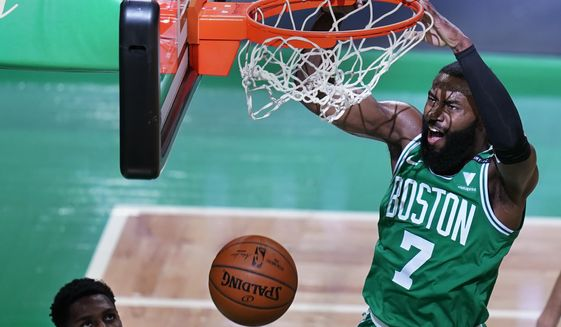 Boston Celtics guard Jaylen Brown (7) dunks against New York Knicks guard RJ Barrett, left, during the first half of an NBA basketball game Wednesday, April 7, 2021, in Boston. (AP Photo/Charles Krupa)
