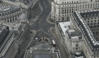 """A view over the City of London looking at the Bank of England, right, from the 59th floor of 22 Bishopsgate in London, Thursday, April 1, 2021. When the pandemic struck, about 540,000 workers vanished from London's financial hub almost overnight. The area known as """"the City"""" became a ghost town as many people began working from home. A year on, most haven't returned to the business hub. While many people believe that post-pandemic workflow will become the new normal, skyscrapers are still rising, and city planners say they aren't worried about empty office blocks. (AP Photo/Alastair Grant)"""