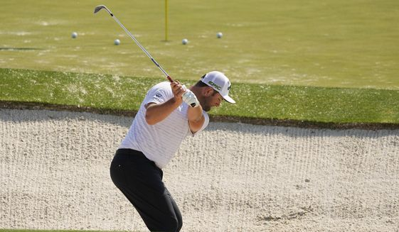 Jon Rahm, of Spain, hits out of a bunker at the driving range during a practice round for the Masters golf tournament on Wednesday, April 7, 2021, in Augusta, Ga. (AP Photo/Charlie Riedel)