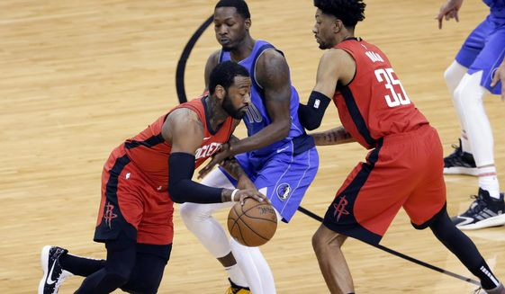 Houston Rockets guard John Wall, left, drives around Dallas Mavericks forward Dorian Finney-Smith (10) as Rockets center Christian Wood (35) sets a screen during the first half of an NBA basketball game Wednesday, April 7, 2021, in Houston. (AP Photo/Michael Wyke, Pool)