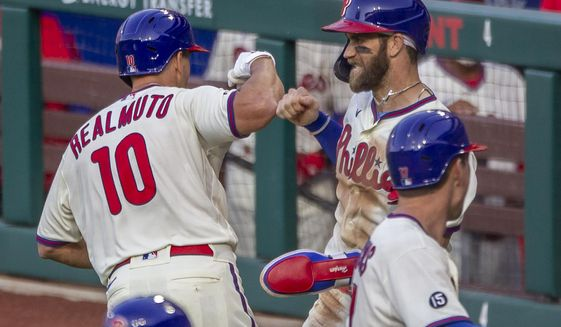 Philadelphia Phillies J.T. Realmuto (10) is congratulated by Bryce Harper after hitting a three run homer during the fifth inning of a baseball game against the New York Mets, Wednesday, April 7, 2021, in Philadelphia. (AP Photo/Laurence Kesterson)
