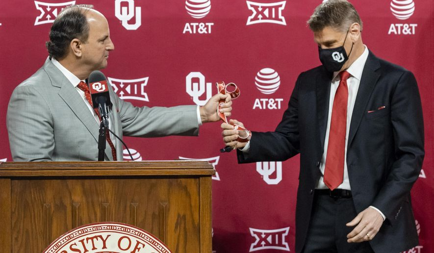 University of Oklahoma vice president and director of athletics Joe Castiglione hands over the coach's whistle to new men's basketball coach Porter Moser during his introductory press conference at Lloyd Noble Center in Norman, Okla., Wednesday, April 7, 2021. (Chris Landsberger/The Oklahoman via AP)