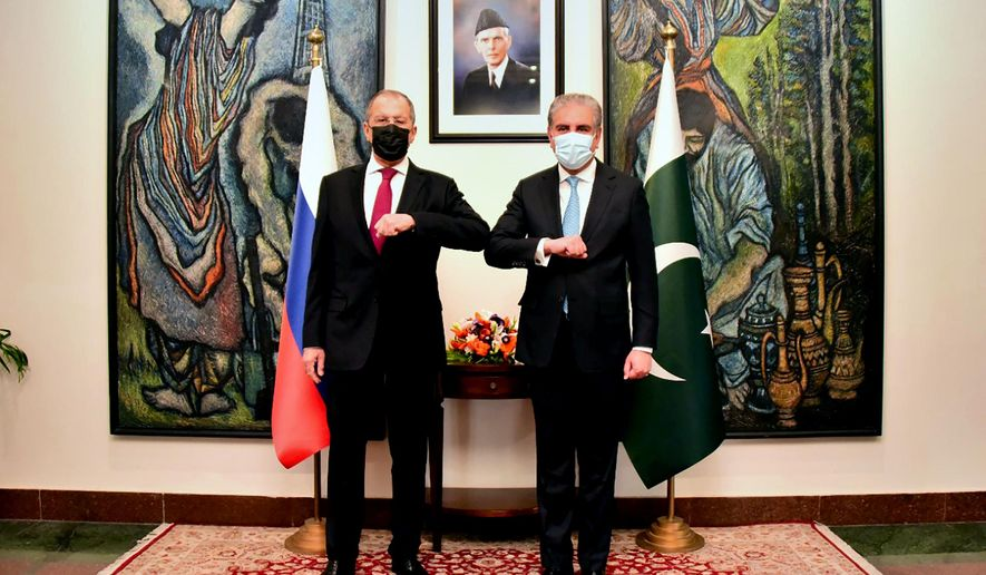 In this photo handout photo released by Pakistan's Ministry of Foreign Affairs, Russia's Foreign Minister Sergey Lavrov, left, bumps elbows with his Pakistani counterpart Shah Mahmood Qureshi prior their meeting, in Islamabad, Pakistan, Wednesday, April 7, 2021. Russia's foreign minister is in Pakistan for a two-day visit expected to focus on efforts to bring peace to neighboring Afghanistan. Lavrov's visit comes as a May 1 deadline for U.S. troops to leave Afghanistan in line with a deal Washington signed a year ago with the Taliban seems increasingly unlikely. (Pakistan's Ministry of Foreign Affairs via AP)