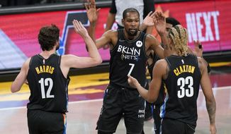 Brooklyn Nets' Kevin Durant (7) high-fives teammates Joe Harris (12) and Nicolas Claxton (33) during the first half of an NBA basketball game against the New Orleans Pelicans Wednesday, April 7, 2021, in New York. (AP Photo/Frank Franklin II)