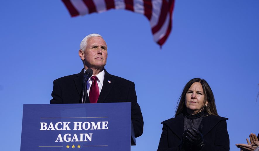FILE - In this Jan. 20, 2021, file phot, former Vice President Mike Pence speaks after arriving back in his hometown of Columbus, Ind., as his wife Karen watches. Pence is steadily re-entering public life as he eyes a potential run for the White House in 2024. He's writing op-eds, delivering speeches, preparing trips to early voting states and launching an advocacy group likely to focus on promoting the accomplishments of the Trump administration. (AP Photo/Michael Conroy, File)