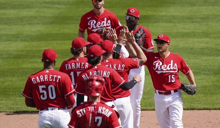 Cincinnati Reds' teammates celebrate after defeating the Pittsburgh Pirates 11-4 at Great American Ball Park in Cincinnati, Wednesday, April 7, 2021. (AP Photo/Bryan Woolston)