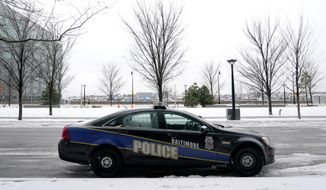 In this Thursday, Feb. 18, 2021, file photo, a Baltimore police cruiser is seen parked near a building while officers check on a call. A comprehensive package of police reform measures cleared the Maryland General Assembly on Wednesday, April 7, 2021, including repeal of police job protections long cited as a barricade to accountability. (AP Photo/Julio Cortez, File)