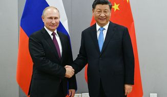 """FILE - In this Nov. 12, 2019, file photo, Russian President Vladimir Putin, left, and China's President Xi Jinping shake hands prior to their talks on the sideline of the 11th edition of the BRICS Summit, in Brasilia, Brazil. Putin and Xi have developed strong personal ties helping bolster a """"strategic partnership"""" between the two former Communist rivals. (Ramil Sitdikov/Sputnik, Kremlin/Pool Photo via AP, File)"""