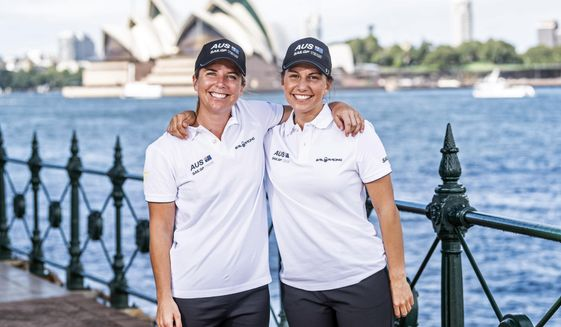 In this photo provided by SailGP are Nina Curtis, left, and Lisa Darmanin at Sydney Harbour in Australia on Wednesday, April 7, 2021. Four years ago, the closest Australian Olympic sailing medalists Darmanin and Curtis could get to the America's Cup was by taking jobs in a hospitality lounge on site in Bermuda. They'll be back in Bermuda in just a few days, this time with the defending champion Australian team in SailGP as part of a developmental program designed to fast-track the inclusion of women into the global league. (SailGP via AP)