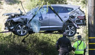 In this Feb. 23, 2021, file photo, a crane is used to lift a vehicle following a rollover accident involving golfer Tiger Woods, in the Rancho Palos Verdes suburb of Los Angeles. The Los Angeles County sheriff plans to announce Wednesday, April 7, 2021, what caused Woods to crash an SUV in Southern California earlier in the year, seriously injuring himself in the wreck. (AP Photo/Ringo H.W. Chiu, File)
