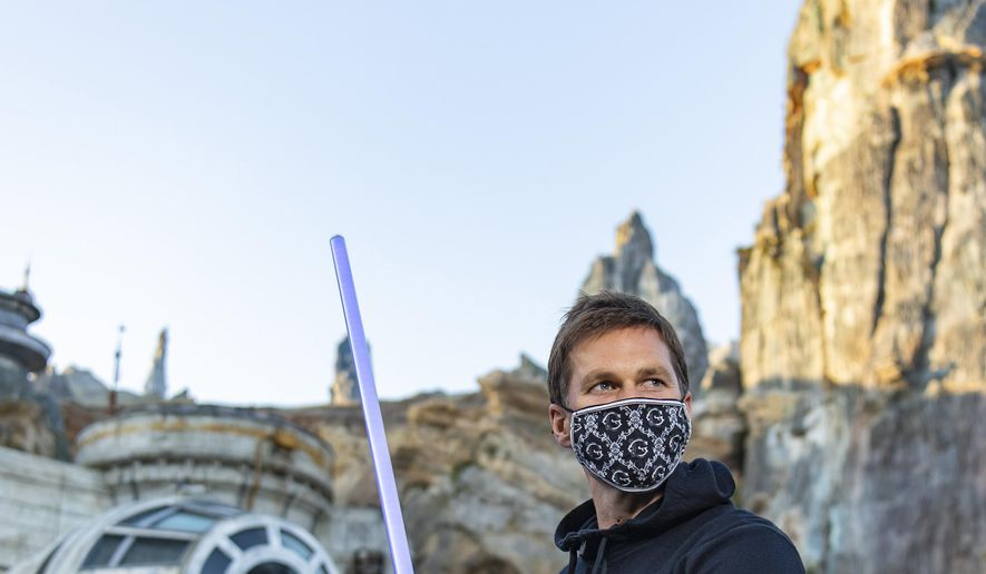 In this photo provided by Walt Disney World, NFL star Tom Brady visits Star Wars: Galaxy's Edge inside Disney's Hollywood Studios at Walt Disney World Resort in Lake Buena Vista, Fla., Monday, April 5, 2021. A mask-wearing Brady visited the Star Wars-themed section of Walt Disney World with his family and friends, two months after he led the Bucs to a Super Bowl win against the Chiefs. (Matt Stroshane/Disney World via AP)