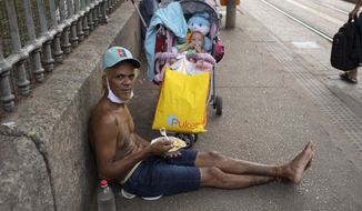 A man looks at the camera as he eats a meal donated by the Leao Xlll Foundation amid the COVID-19 pandemic in Rio de Janeiro, Brazil, Wednesday, April 7, 2021. (AP Photo/Silvia Izquierdo)