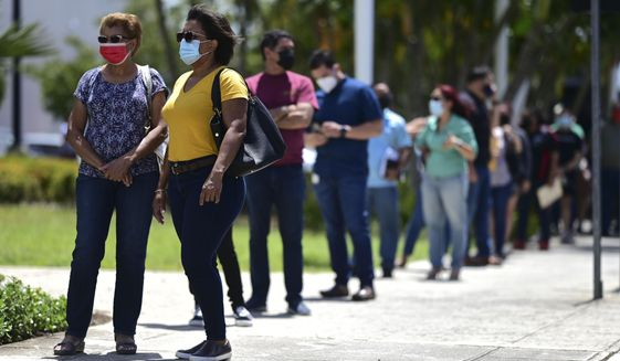 People line up outside the Miramar Convention Center for the first mass vaccination event carried out by the Department of Health and the Voces nonprofit organization, seeking to apply 10,000 Johnson and Johnson vaccines, in San Juan, Puerto Rico, Wednesday, March 31, 2021. (AP Photo/Carlos Giusti)